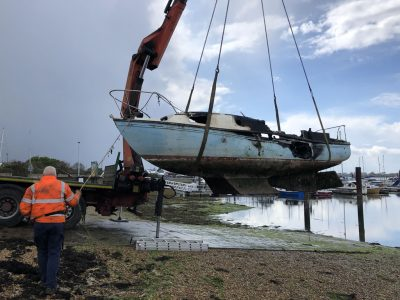 Abandoned Yacht Collection Saga - Burnt yacht being lifted onto transport