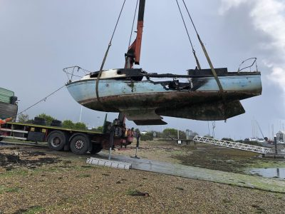 Abandoned Yacht Collection Saga - Burnt Yacht being lifted onto a trailer.