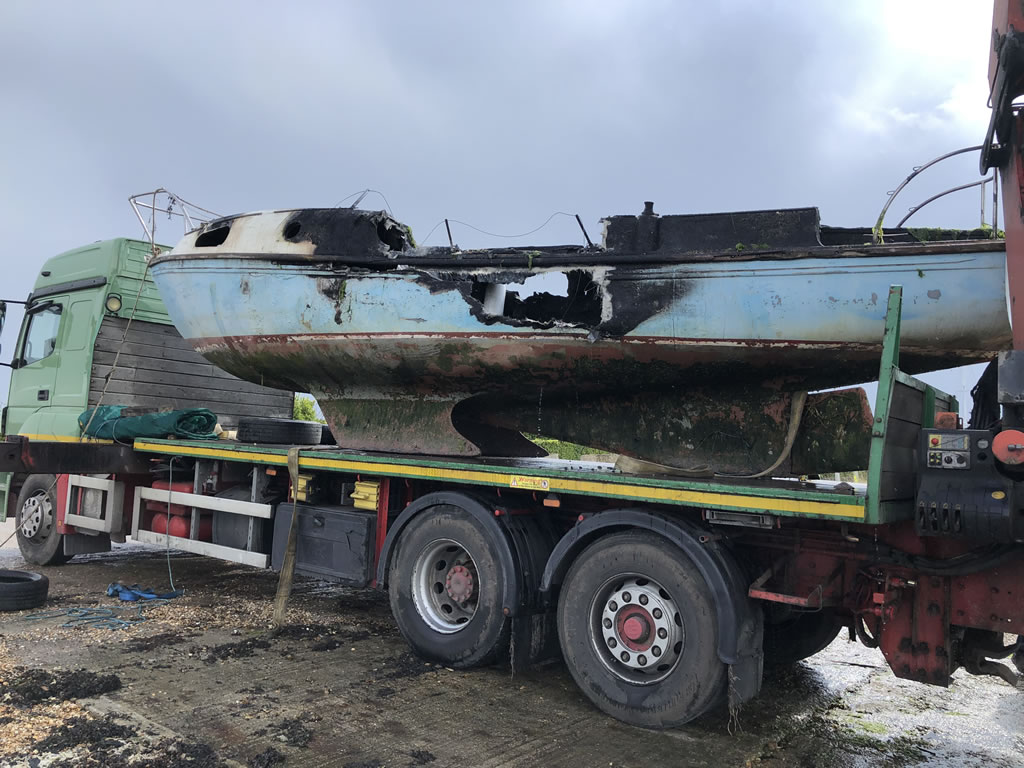 Abandoned Yacht Collection Saga - Burnt yacht on transport