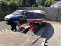 scrap yacht in a car park - Yacht being loaded onto the trailer